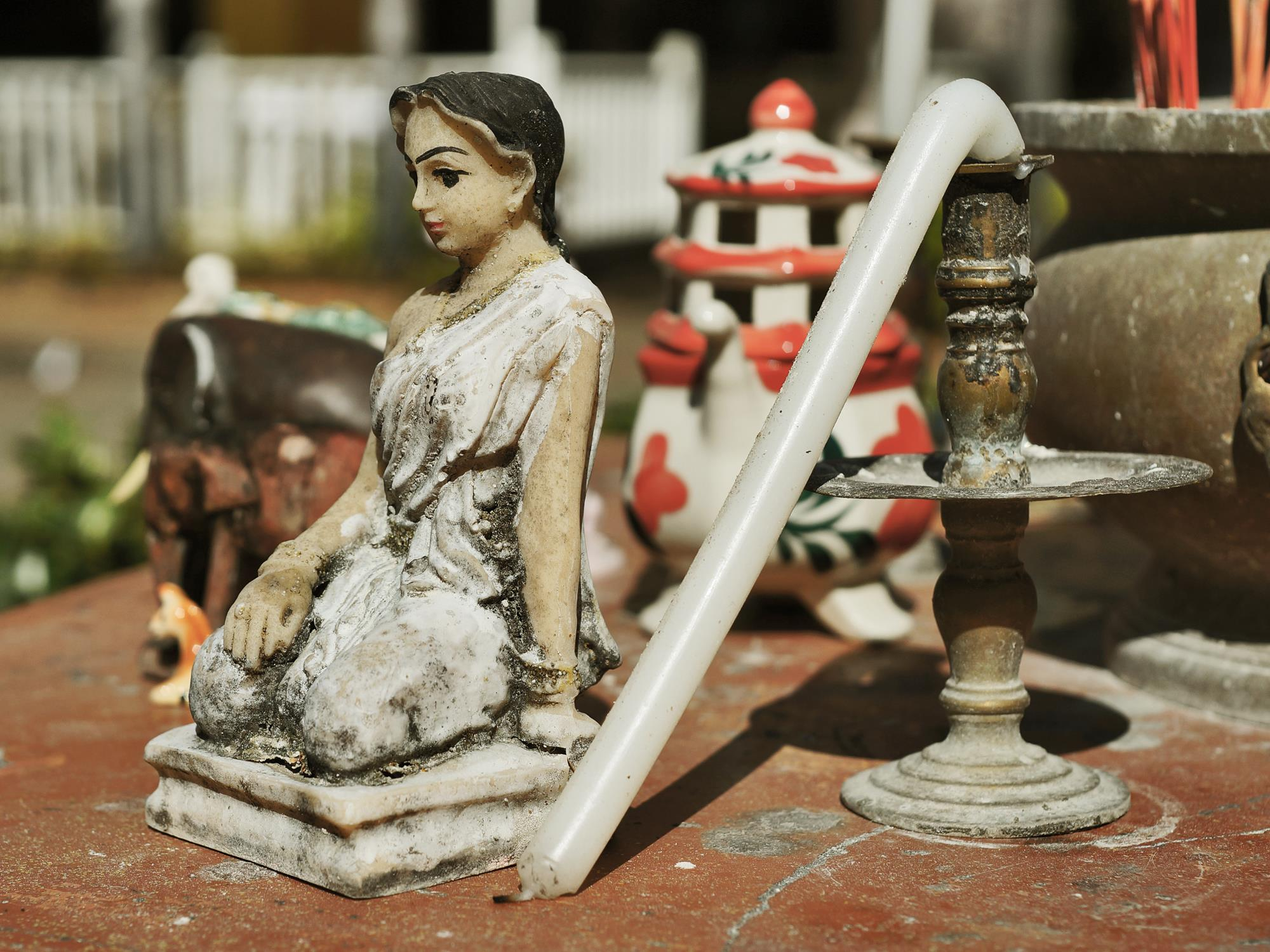 thai buddhist figurine with melted candle