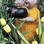 three buddhist statues and flowers