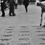 man drawing chinese characters on floor