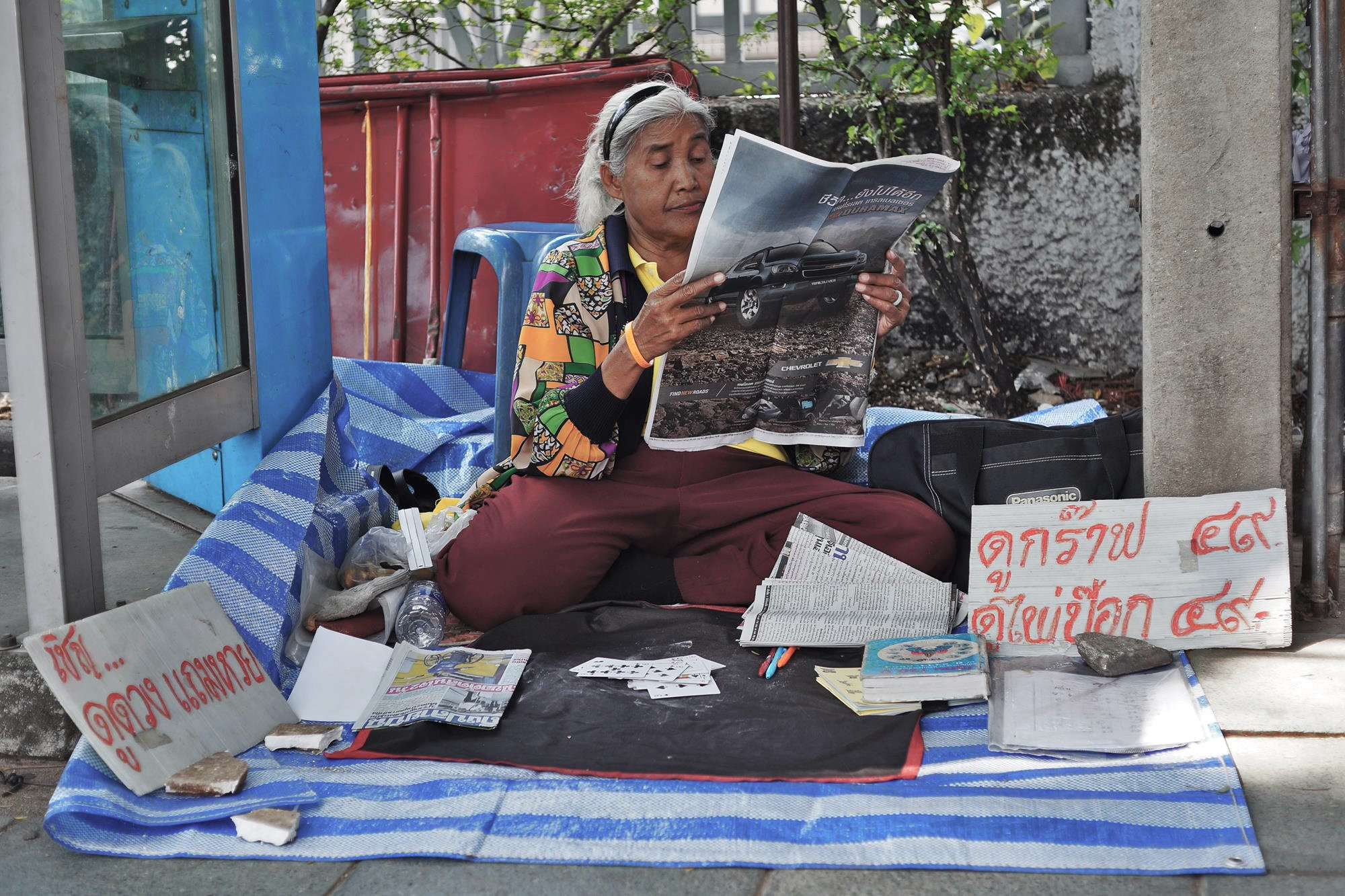 woman reading newspaper bangkok thailand